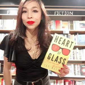 Photo of author Ivy Ngeow holding her book, Heart of Glass